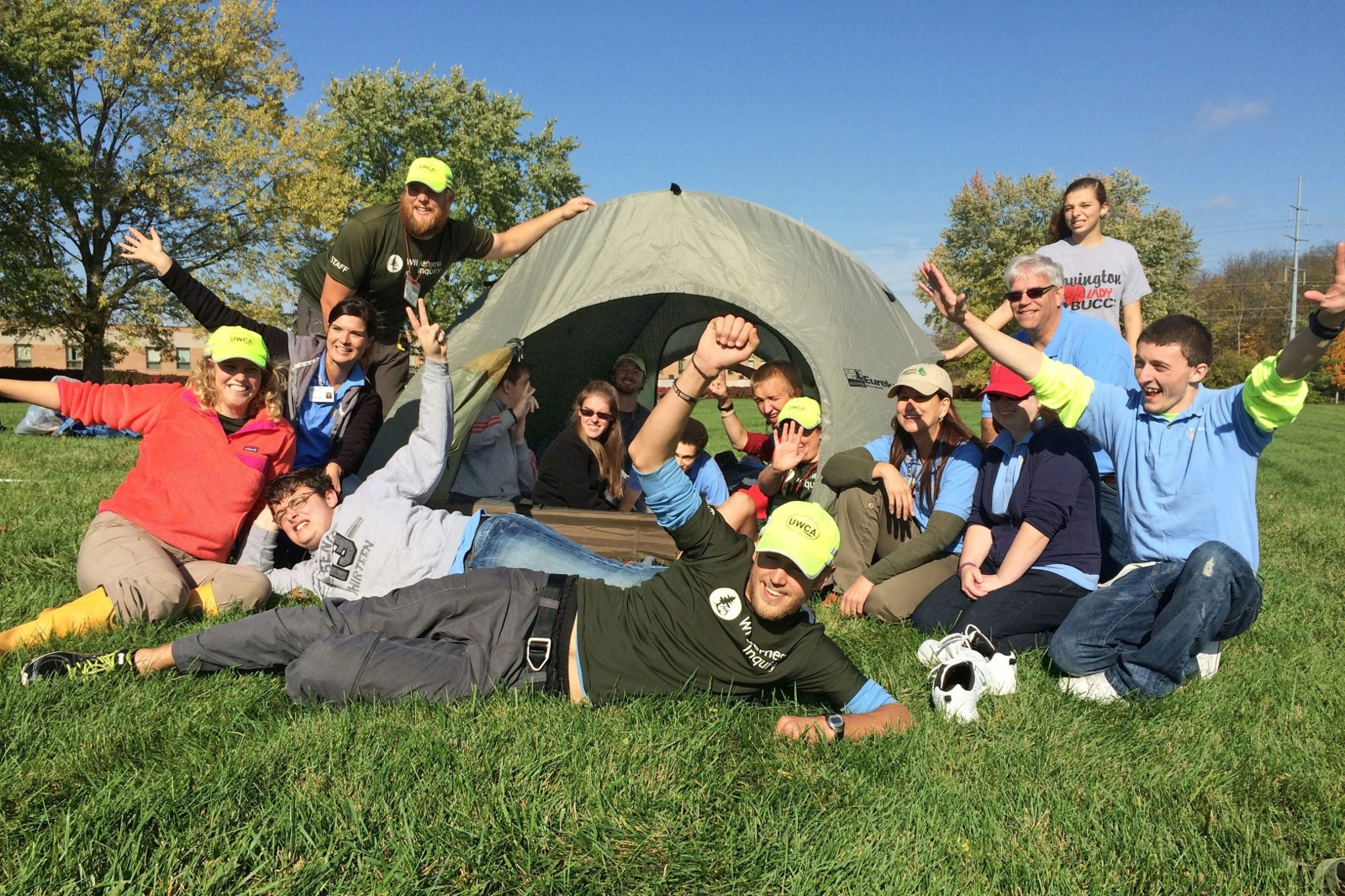 a group photo of people in and outside of a tent in a field