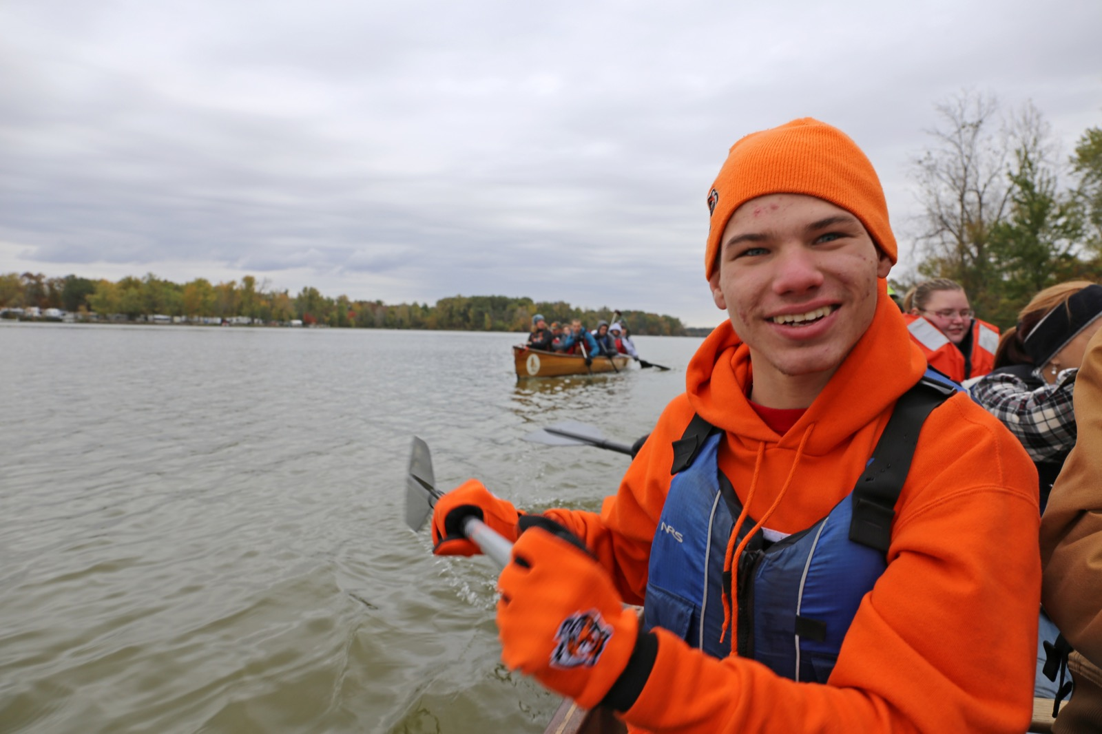 a photo of a male participant smiling while he helps  paddle the voyageur canoe in the fall
