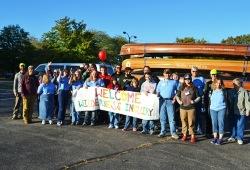 photo of participants and staff in front of canoes Participants hold a welcome sign for Wilderness Inquiry