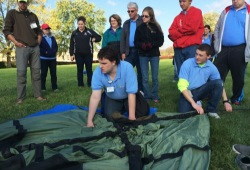Group of participants learn how to set up a tent in Troy
