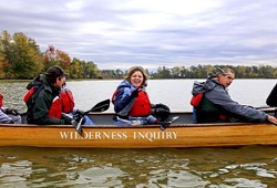 a photo of participants enjoying the calm day on the lake in the voyageur canoe in the fall