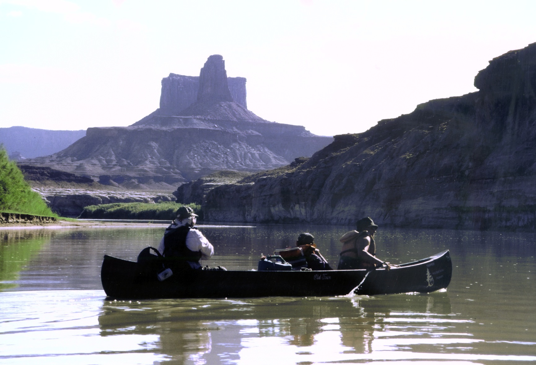 A tandem canoe with three participants paddles around a river bend and towards a butte on the Green River.