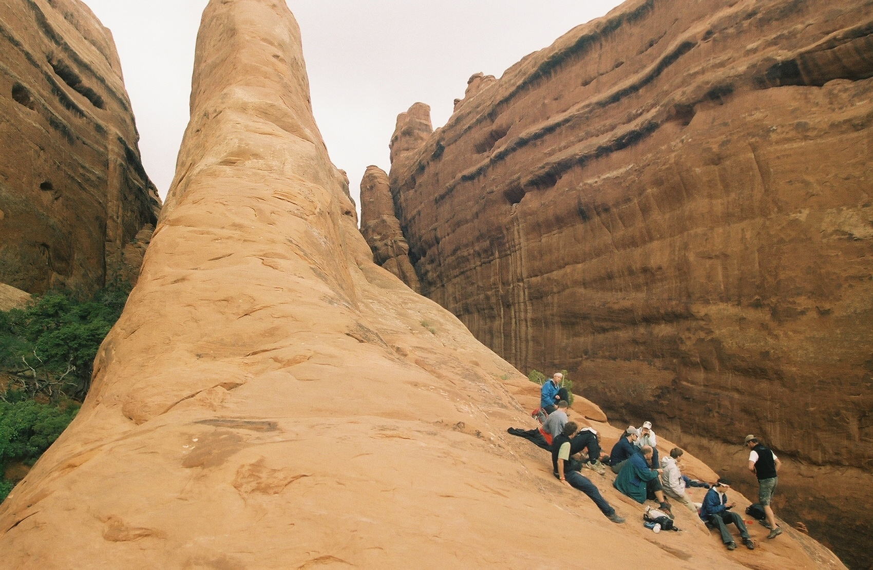 Participants sit on a smooth rock face as they take a break from canoeing to explore the side canyons of the Green River.