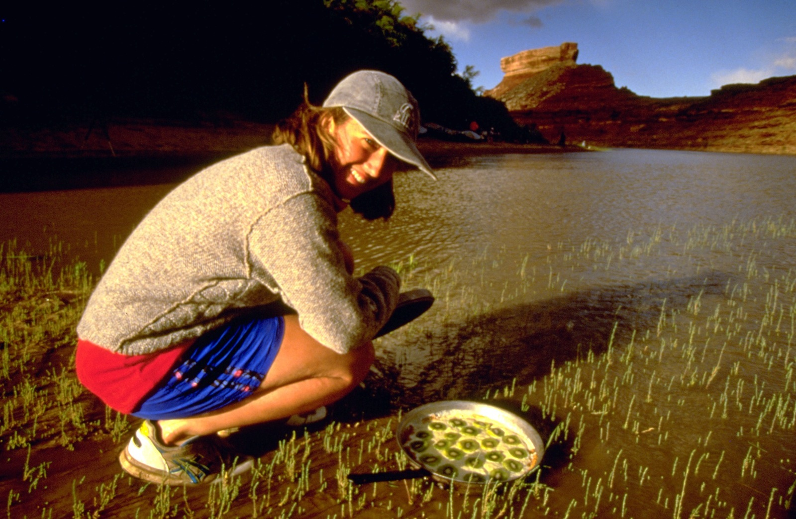 A participant puts the pan of dessert in the Green River to cool before eating.