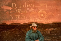 "A man poses with an inscription on a red rock canyon wall that reads ""D. Julien May 3, 1836"""