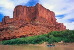 A tandem canoe sits in the water near a shore with green tamarisk and imposing red rock formations in the background.