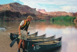 A man pulls 5 Wilderness Inquiry canoes ashore on the Green River with large rock formations in the background.