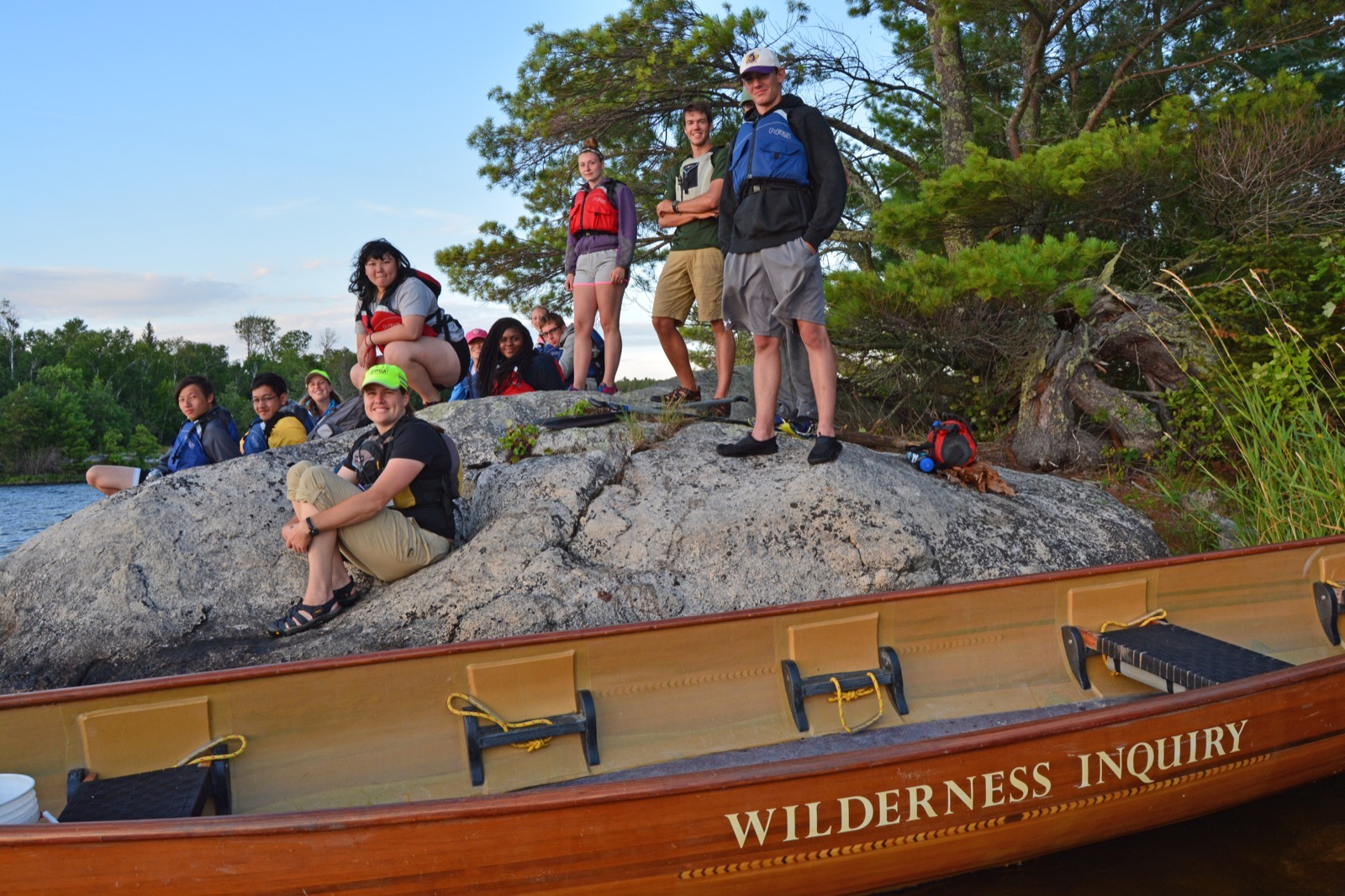 Group of participants relax on a large rock by the lake in Voyageurs National Park