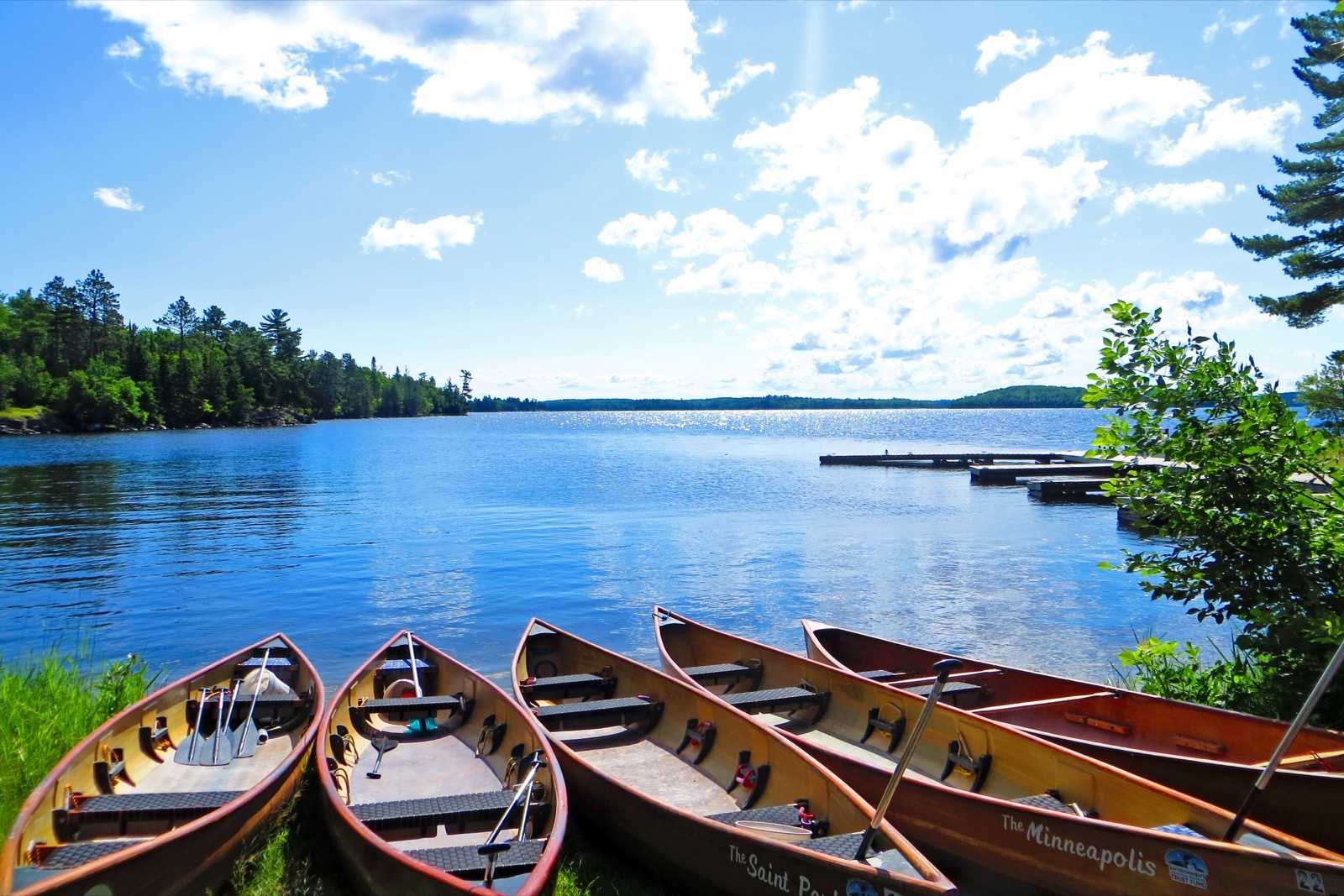 Five canoes lined up on the shore of a large lake on a sunny day at Voyageurs National Park.