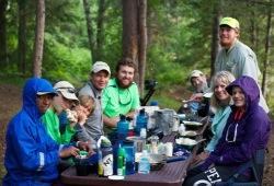 Group of nine enjoy a meal at the dinner table at their campsite.