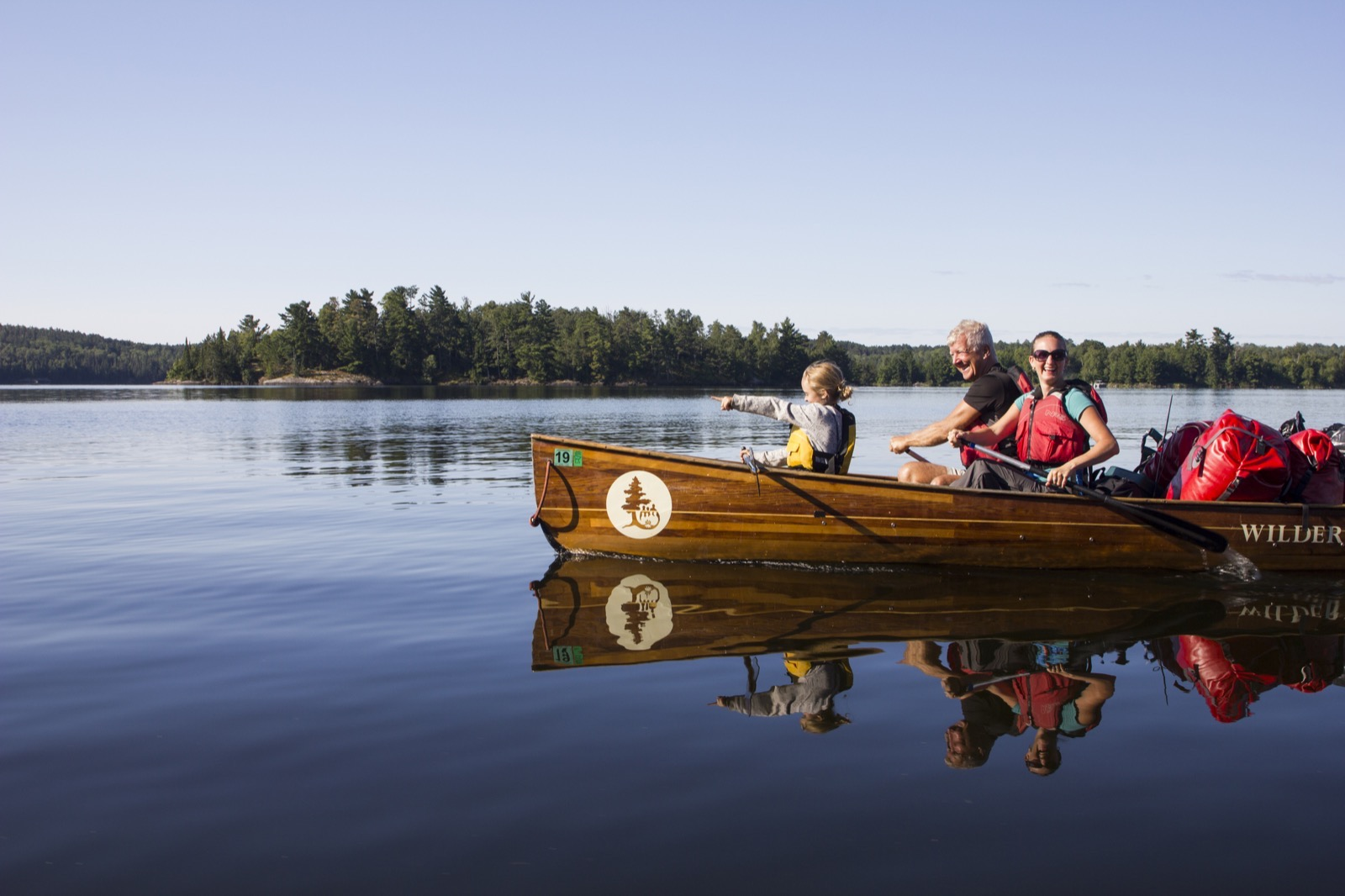 While paddling away from their campsite, a family group in a Voyageur canoe poses for a photo with water and pine trees in the background.