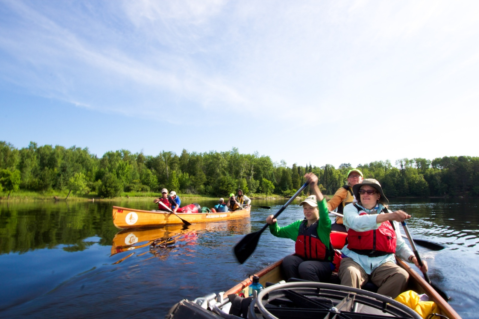 Two Voyageur canoes loaded up with gear and paddlers set out across the lake on a sunny day.