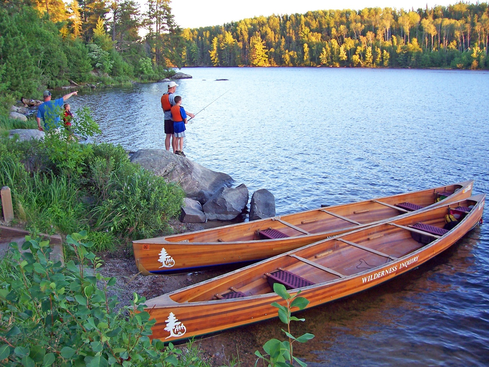 A father and son fish next to two canoes on a rocky shore in Voyageurs National Park.
