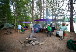 Scene of a group at the campsite, including tents, two tarps, camp kitchen, and fire pit.