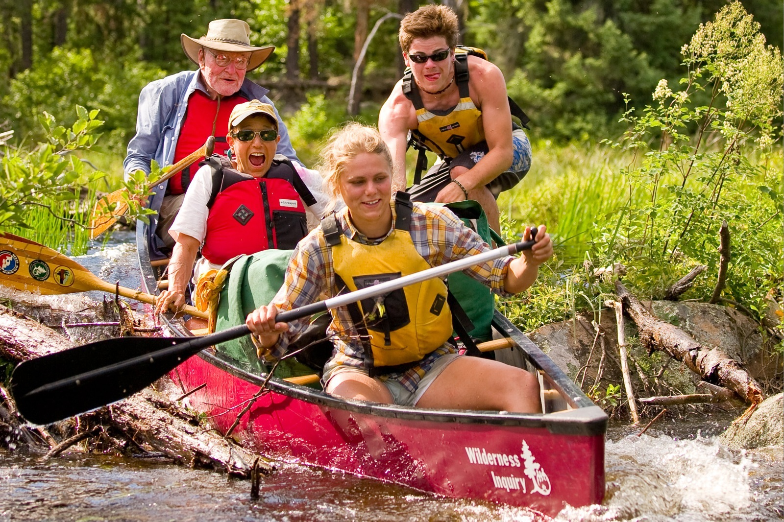 Wilderness Inquiry staff gives a canoe of excited participants a push over a beaver dam in the Wabakimi Wilderness.