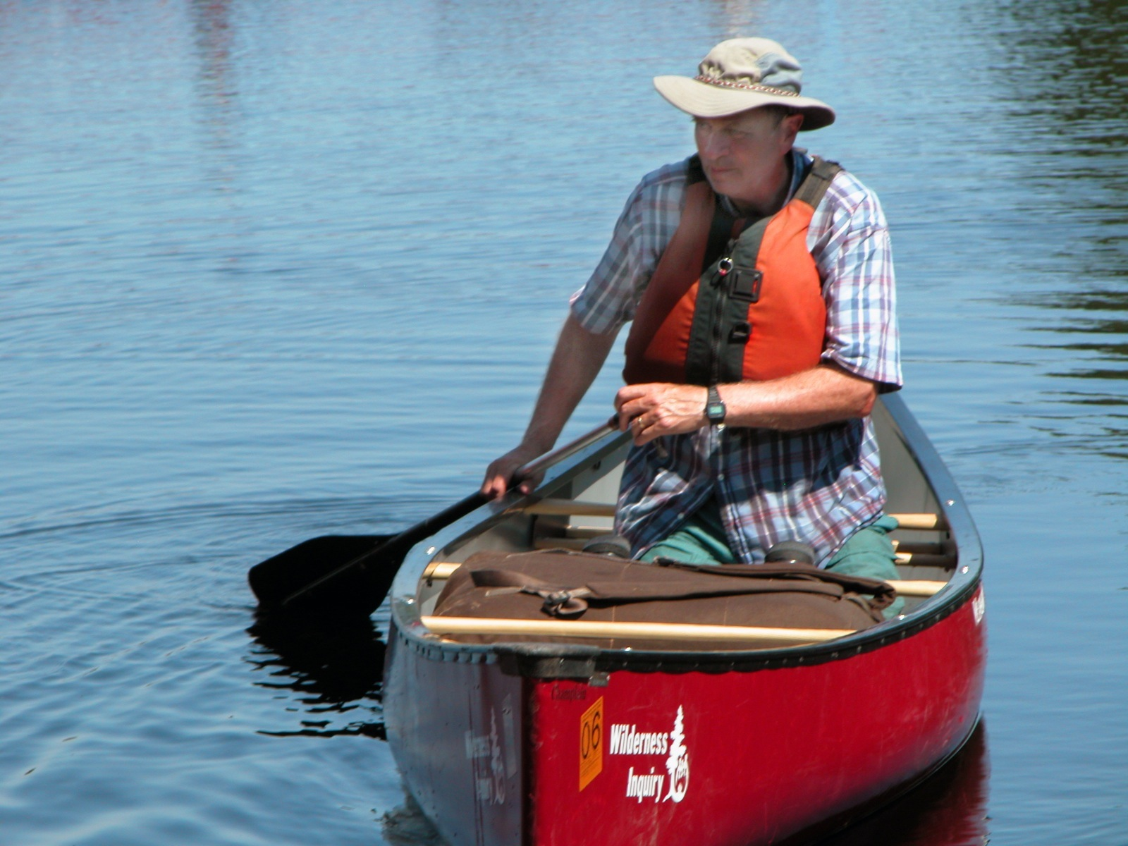 A man paddles a red canoe solo on calm water in the Wabakimi Provincial Park.