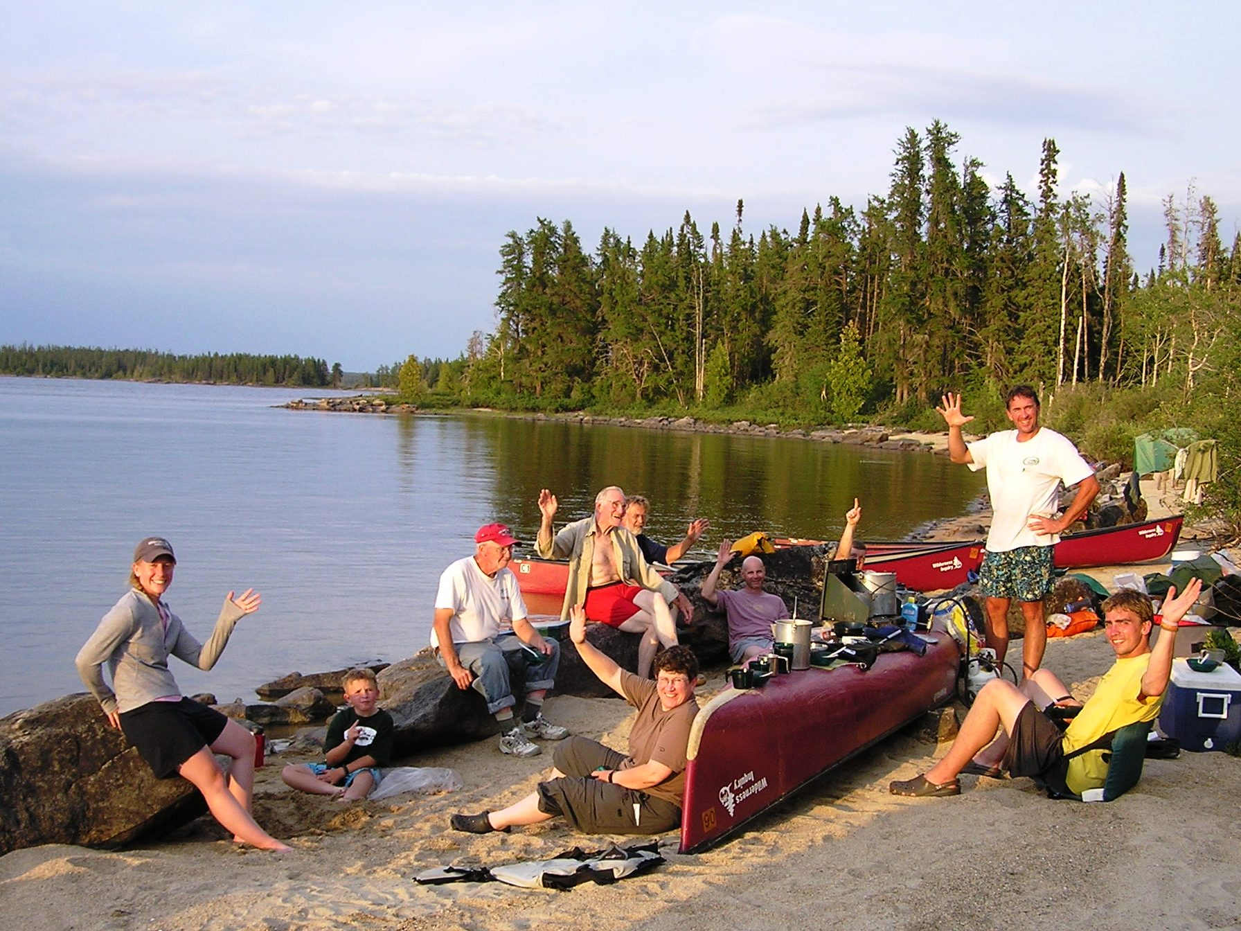 A group waves while eating lunch on a beach with tree-lined shores on a calm lake in the background.