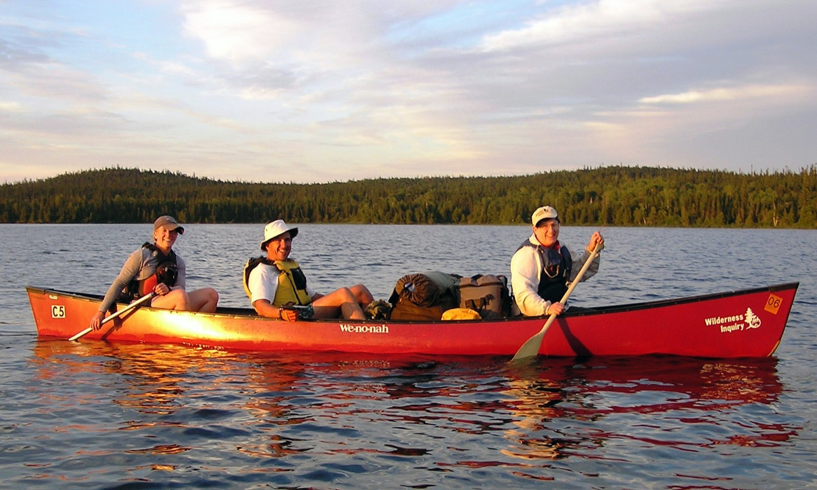 Three paddlers in a Wenonah canoe in the Wabakimi Provincial Park at dusk.