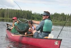 A man and two kids in a tandem canoe pull a large northern pike from the water using a net.