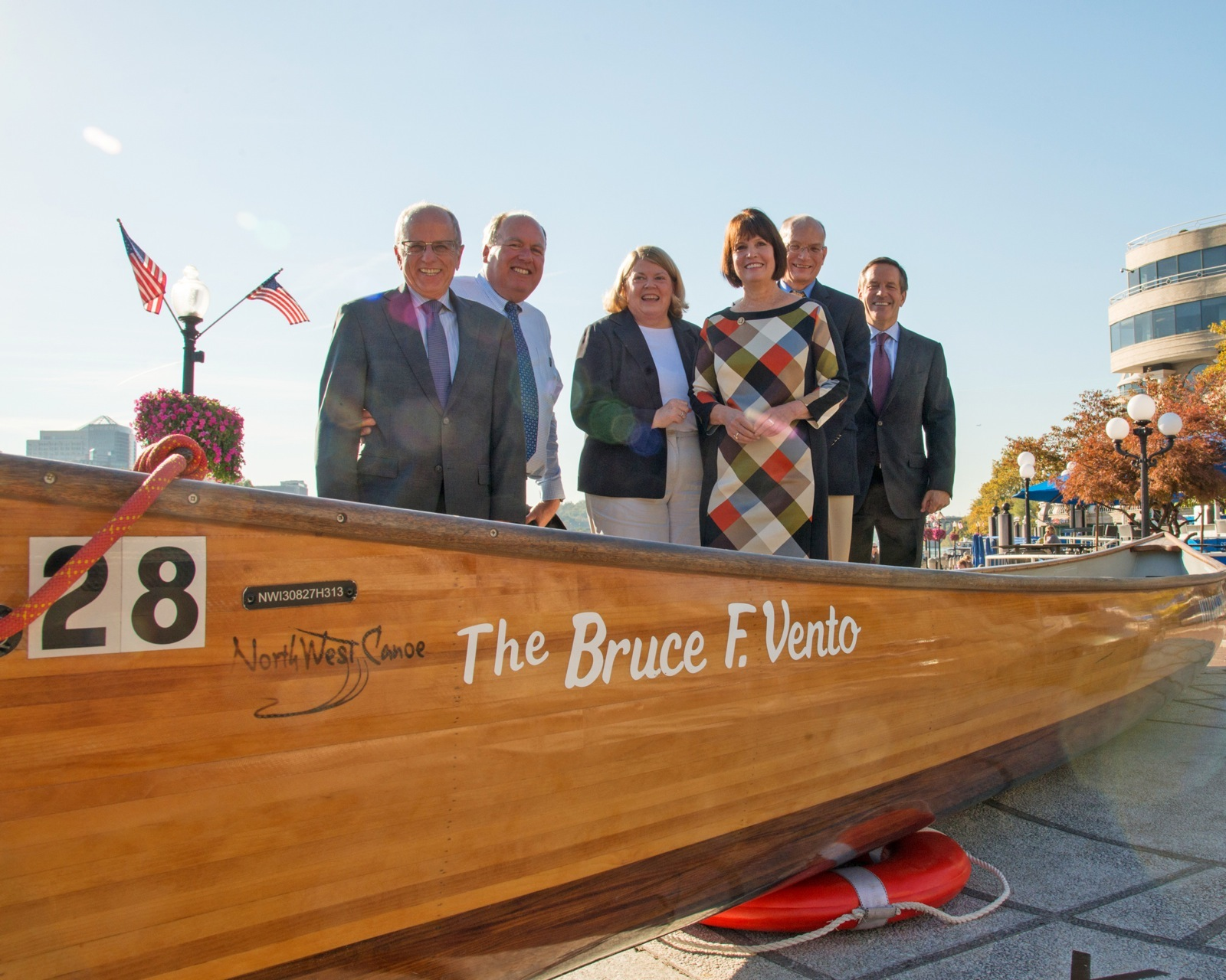 Wilderness Inquiry staff and RBC staff smile in front of the Bruce Vento Voyageur canoe