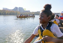 an action photo of a youth paddling the canoe