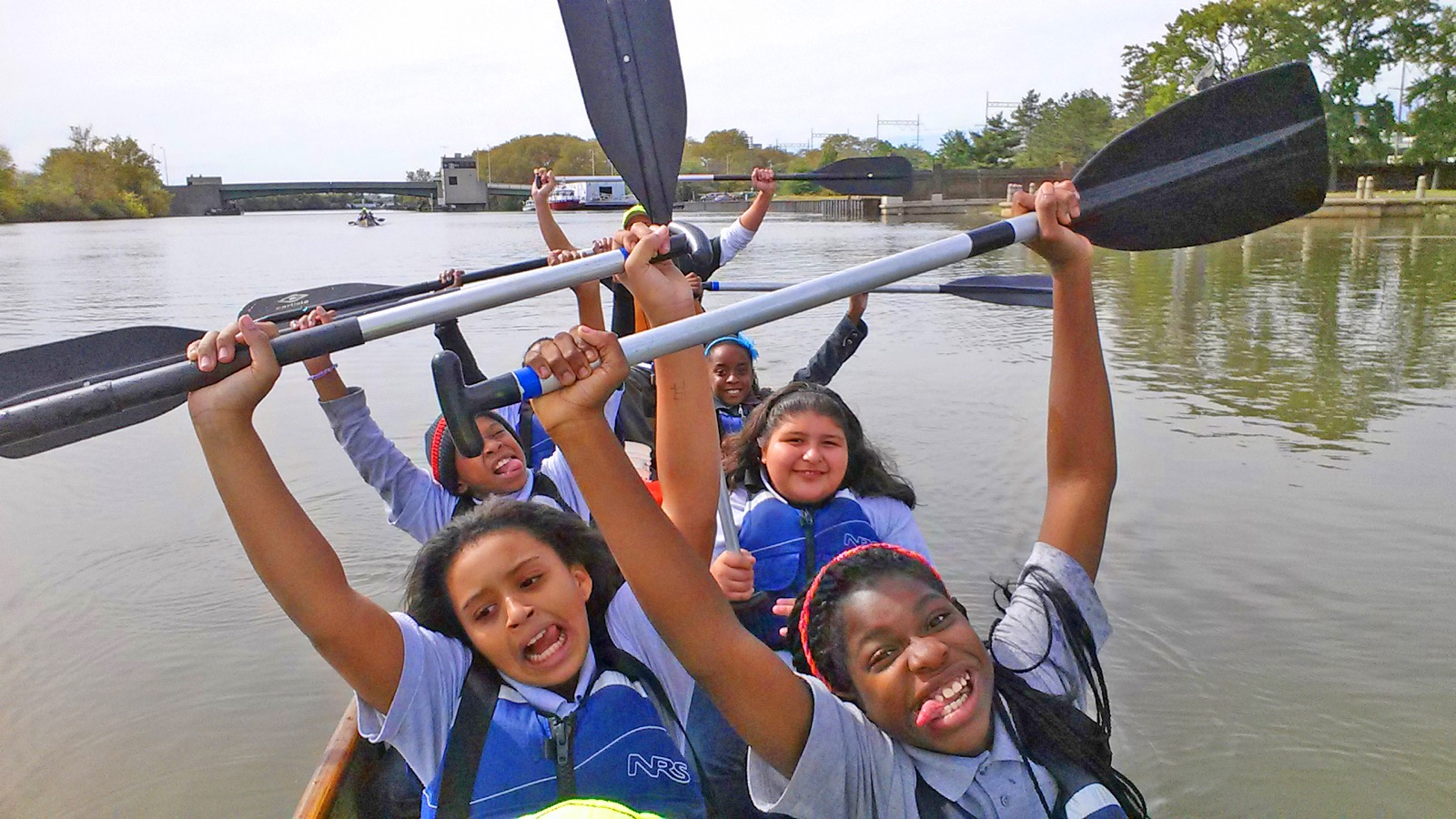 a group photo of participants in their canoe holding the paddles above their heads