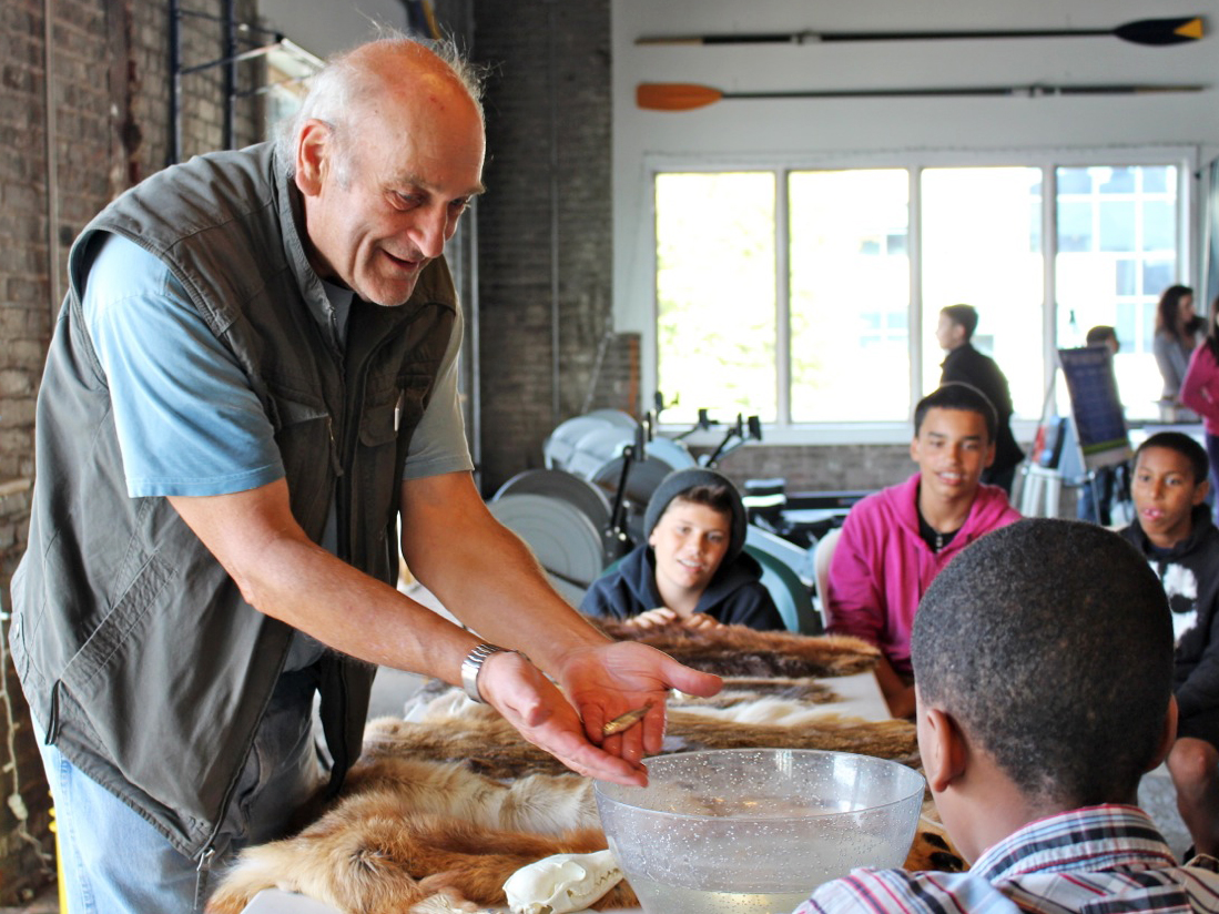 A man teaches students about wildlife of the river with displays and animal fur