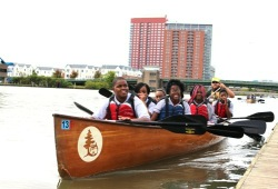 students take their paddles out of the water near the dock for a photo in canoe