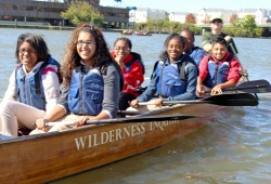 6 students in a canoe smile for the camera as their paddles are out of the water on a sunny day
