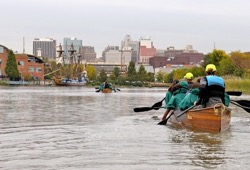 three canoes paddle towards the skyline in Wilmington DE on a cloudy day