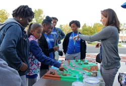 a group of youth learn about water quality with a demonstration