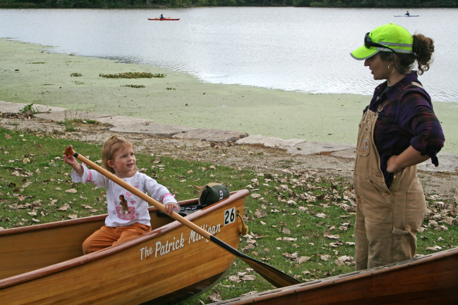 a young girl sits in a canoe on land with large paddle smiling at WI staff member
