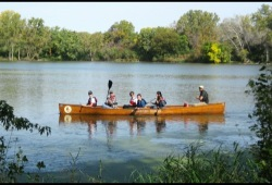 a group of participants paddle their voyageur canoe next to the shore on a river