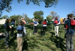 participants stand in a circle on land playing a paddle game before canoeing