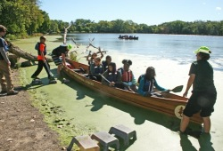 two WI crew hold canoe steady on water for participants to enter