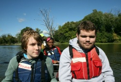 three participants smile for the camera while in the Voyageur canoe