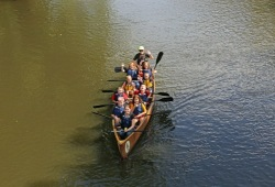 group of youth waving and giving thumbs up to the camera while paddling the canoe along the river