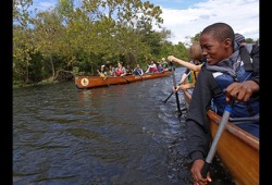 action shot of a boy working on his paddling techniques in a Voyageur canoe