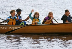 youth smile and wave to camera while paddling their canoe on the lake
