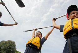 two boys reach their paddles above their heads