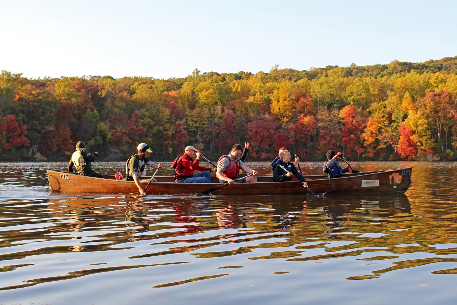 an action shot of participants paddling their canoe along a calm river in the fall