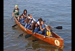 action shot of 8 participants and a staff member paddling their canoe on a body of water
