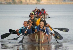 action shot of a group of youth and a staff member paddling the voyageur canoe along the river
