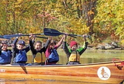 5 youth raise their paddles above their heads while in their voyageur canoe on a sunny day