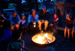 Participants gather around a campfire in the dark to share stories.
