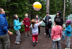 A group of kids play games with a beach ball around the camp site.