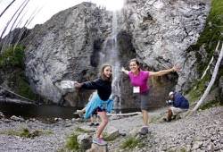 A staff member and young girl test out their balance on a rock in front of a waterfall.