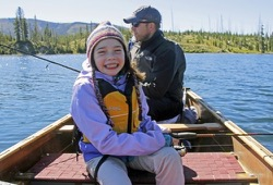Daughter and dad fish from a large canoe on Yellowstone Lake.