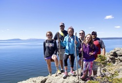 Two families pose in front of Yellowstone Lake.