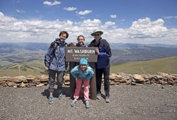Family poses with Mount Washburn sign in Yellowstone.